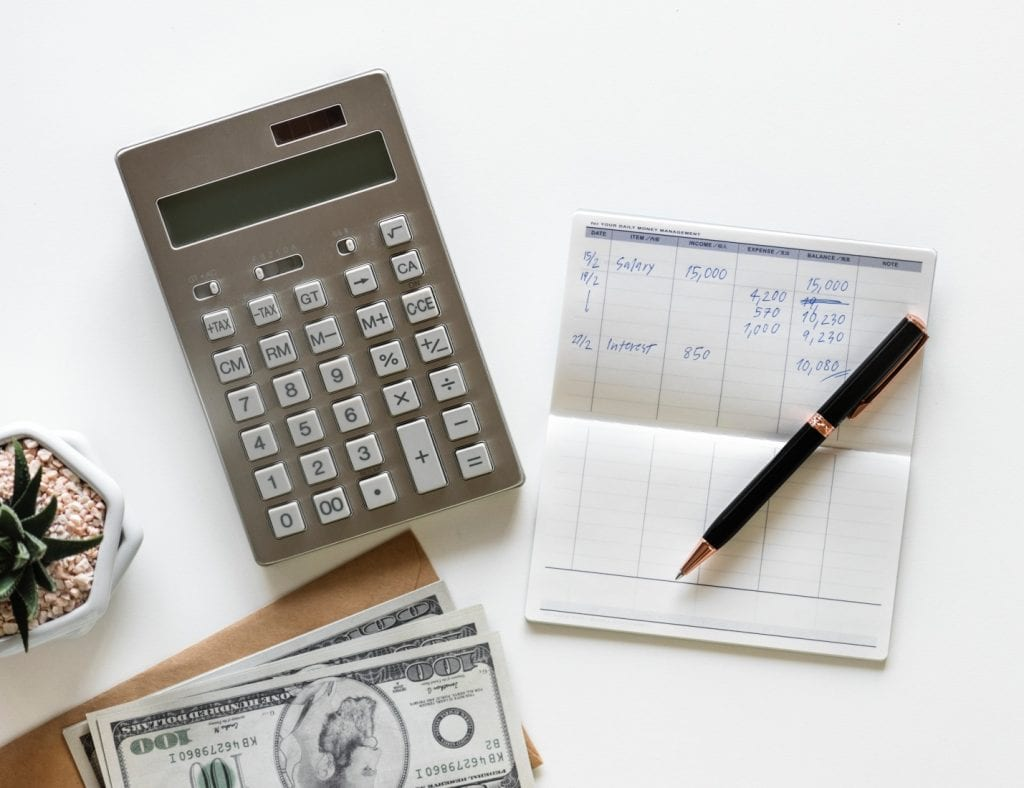 Calculator-between-stack-of-banknote-and-click-pen