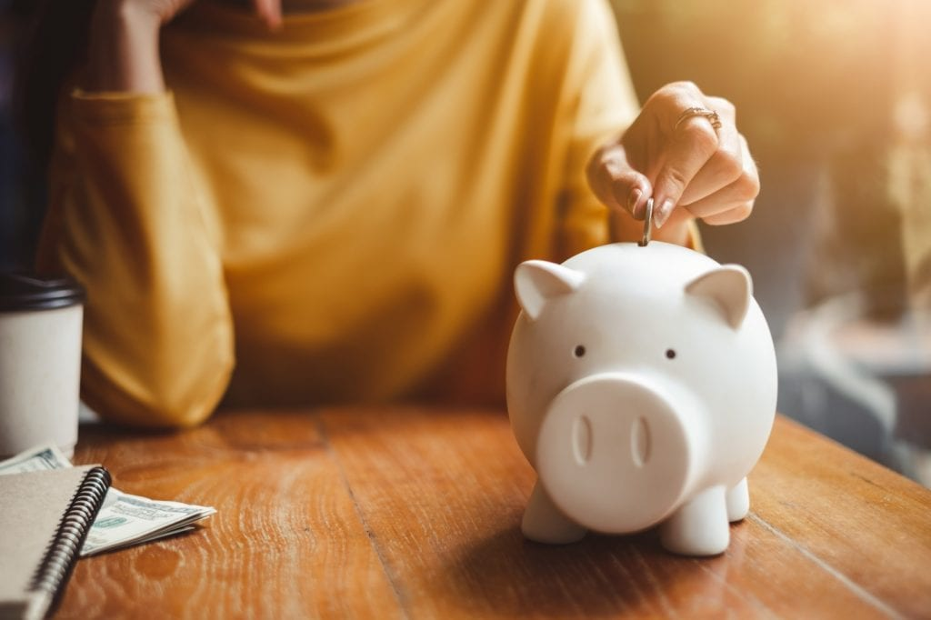 Woman Hand Putting Money Coin Into Piggy Bank